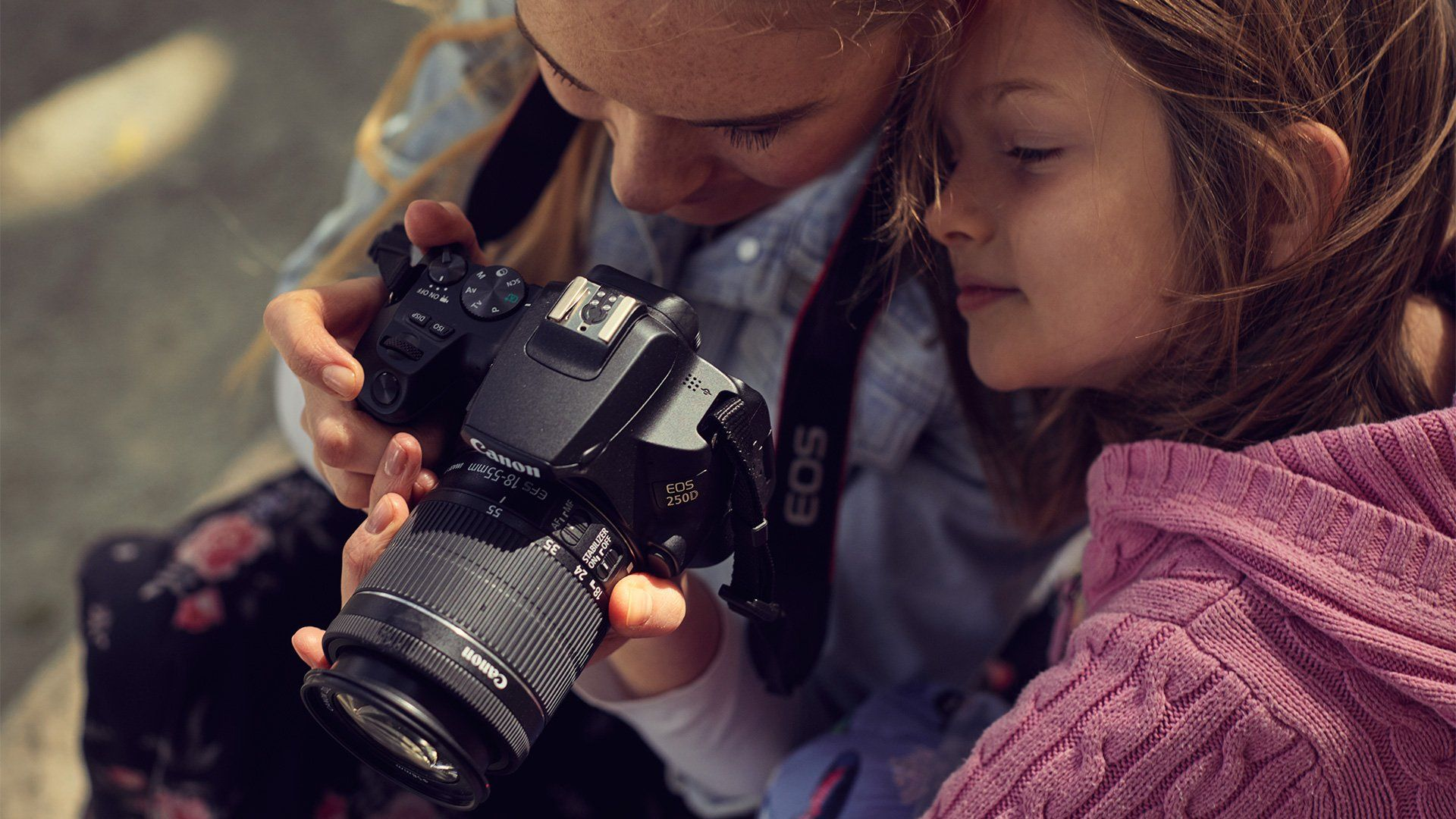A woman lifts a Canon EOS 250D to take a photo of her daughter.